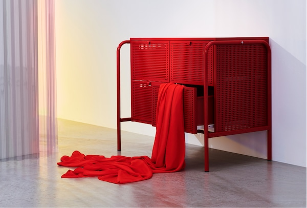 A room with a red NIKKEBY chest of drawers and some red textile hanging from one of the open drawers.