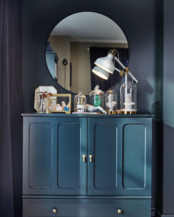 A round mirror, a dark blue-green cabinet and small, decorative items that stand inside glass domes and display boxes.