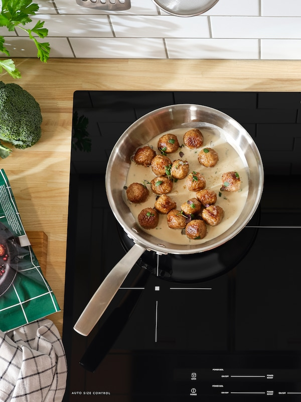 A sauté pan with meatballs and sauce inside stands on a black induction hob.