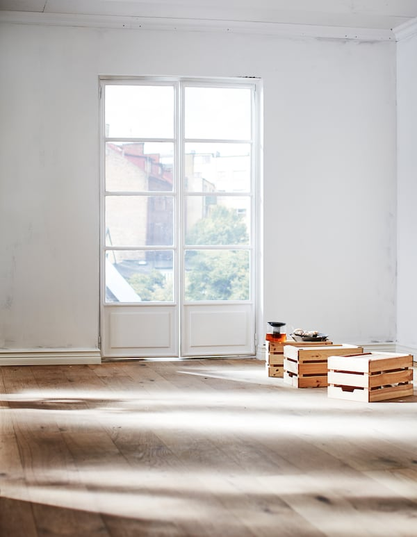 A section of an empty room with a white, unpainted wall and floor in natural wood. Sunlight falls in through French windows.