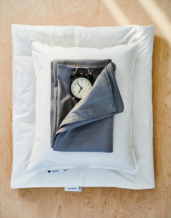 A sheet of plywood with a folded white duvet, a white pillow, dark blue bed linen and an old fashioned black alarm clock.