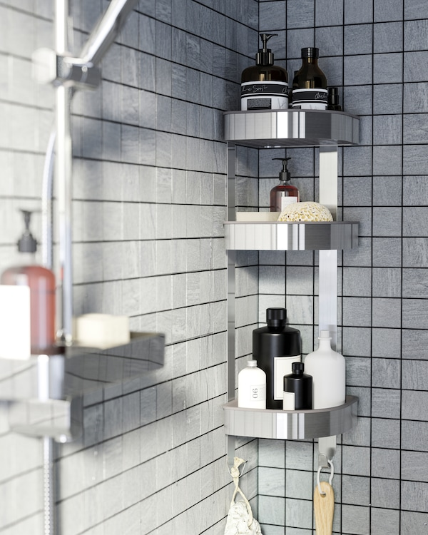 A shower with grey tiles and a corner wall shelf in stainless steel that stores shower gels, shampoos and more.