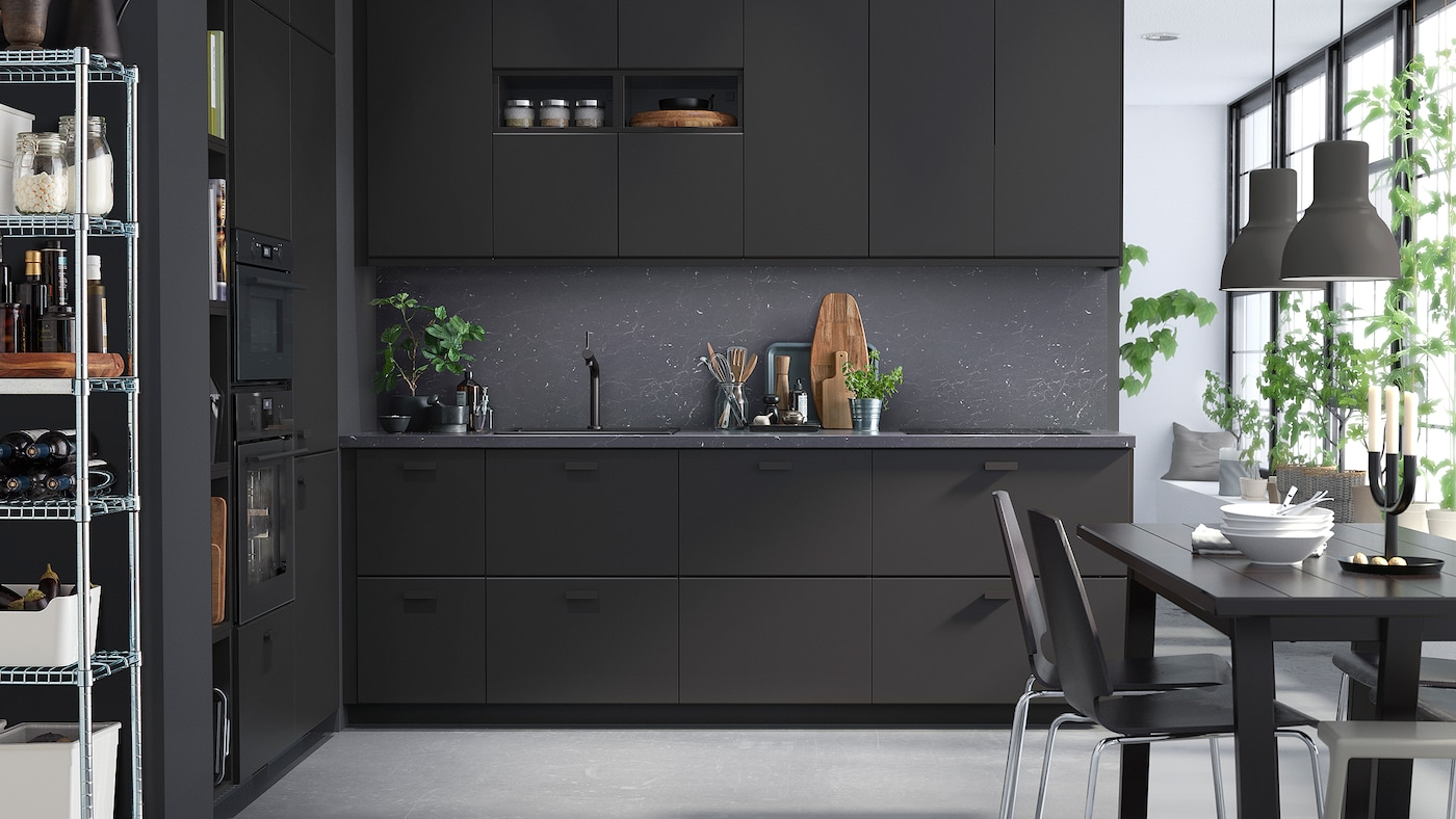 A sleek kitchen with anthracite units, dark grey walls and a black dining table and chairs.