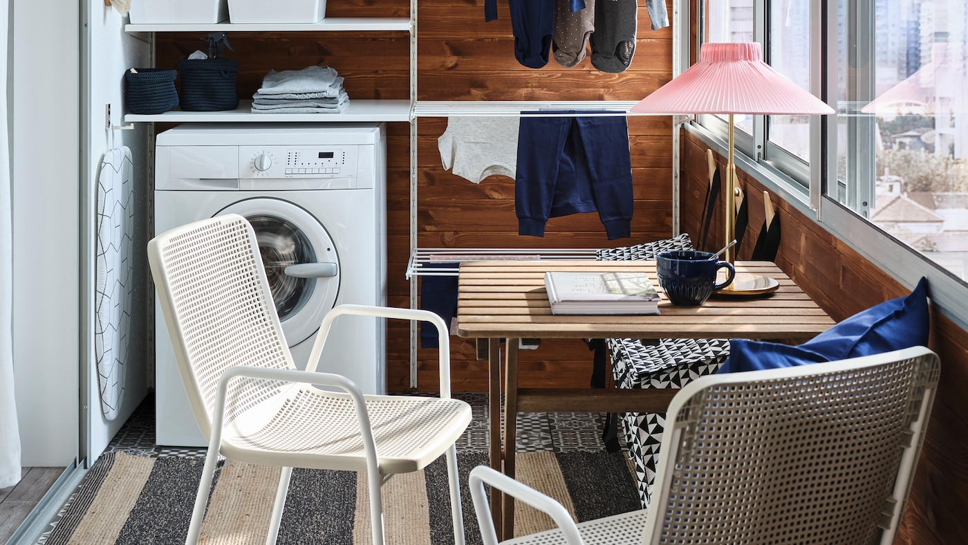 A small balcony with a white storage system for laundry, a washing machine, a small table and two white/beige chairs.