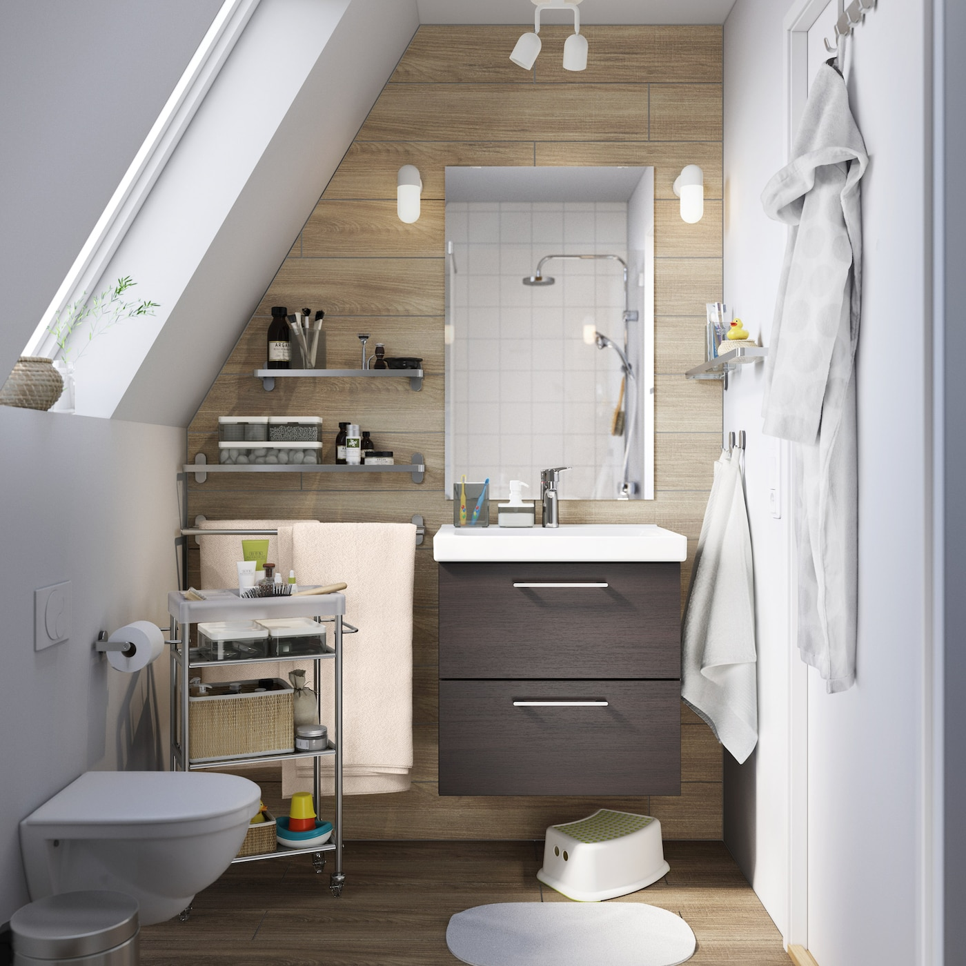 A small brown and white bathroom with a sloping ceiling and brown sink cabinet with drawers.
