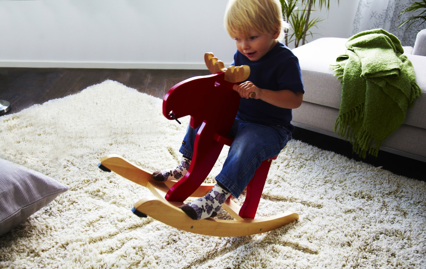 A small child playing on a red moose-shaped rocking horse in a living room with neutral decor.