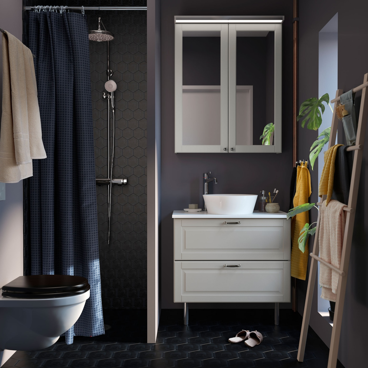A small, dark grey bathroom with white GODMORGON cabinet, TOLKEN countertop and KATTEVIK sink.