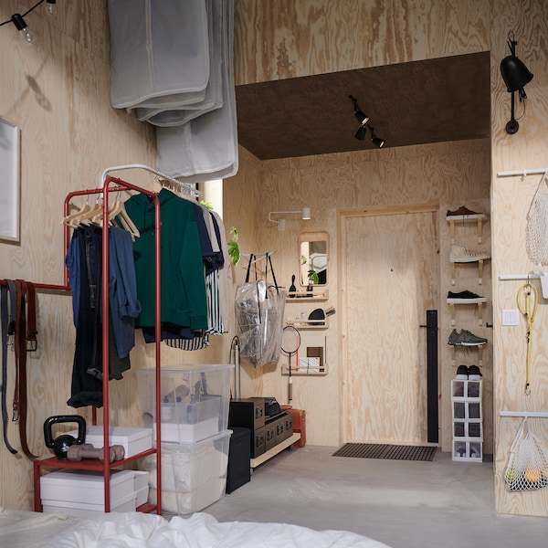 A small hallway with high walls, clothes bars and brackets are mounted vertically to make room for clothes and shoes.