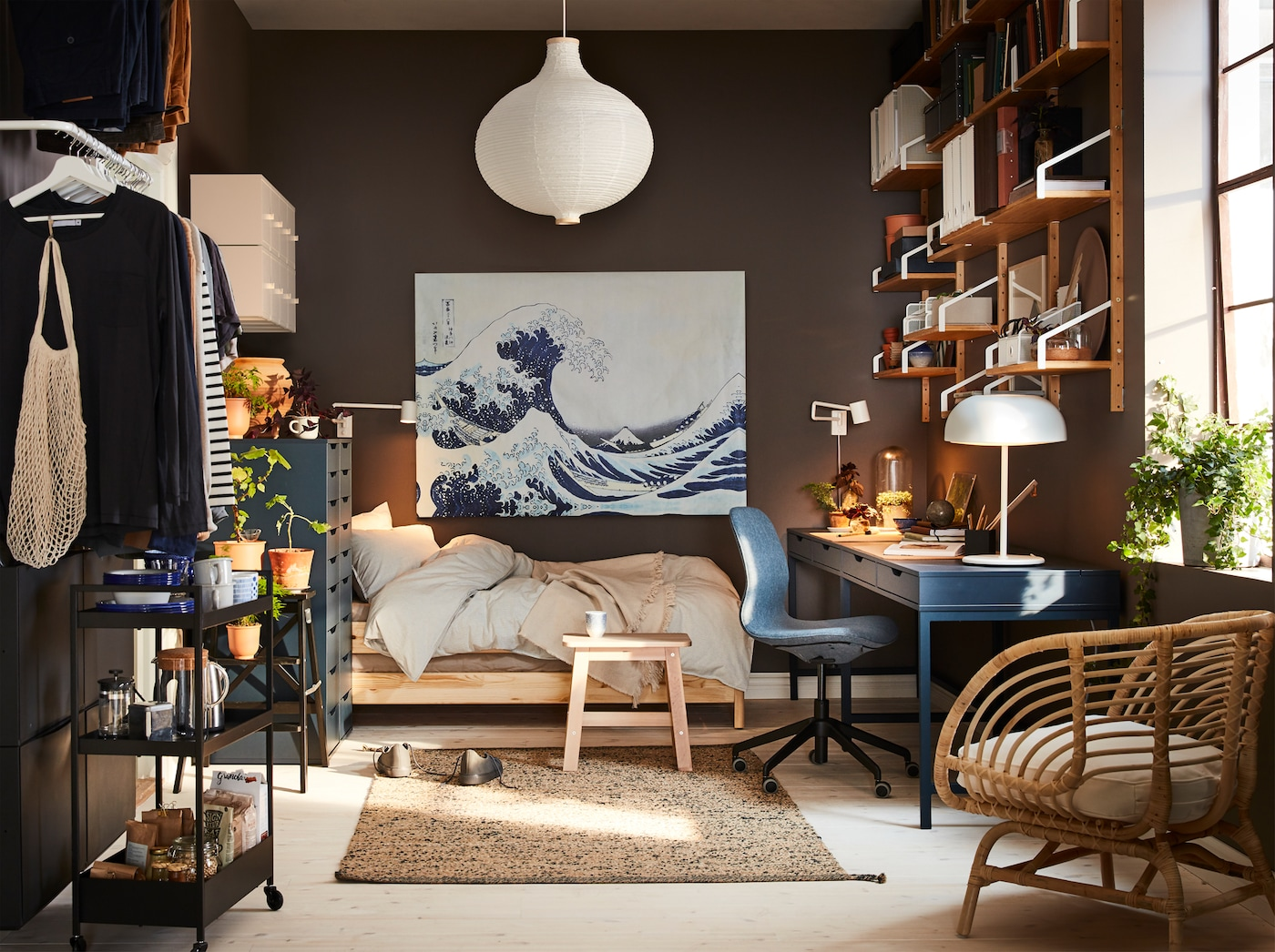 A small home with a dark blue desk, a rattan armchair, a white pendant lamp shade and a painting with a big blue wave.