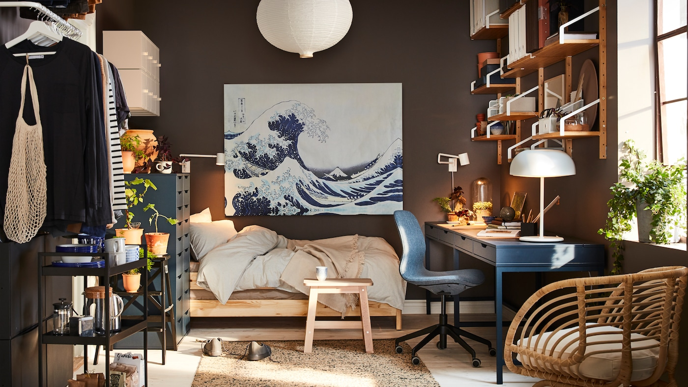 A small home with a dark blue desk, a rattan armchair, a white pendant lamp shade and a painting with a blue wave.