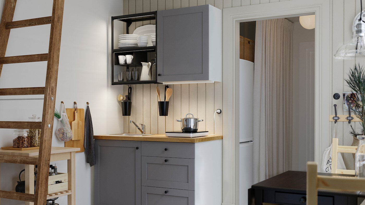 A small kitchen with open shelves in anthracite, grey fronts, a wood worktop, a black table and two wooden chairs.