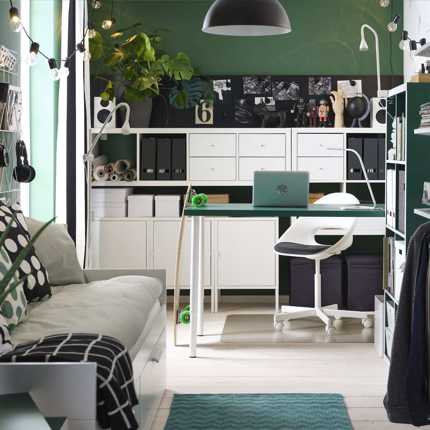 A small, overall green room with a green table, white shelving units, a day-bed, an open wardrobe and a black pendant lamp.