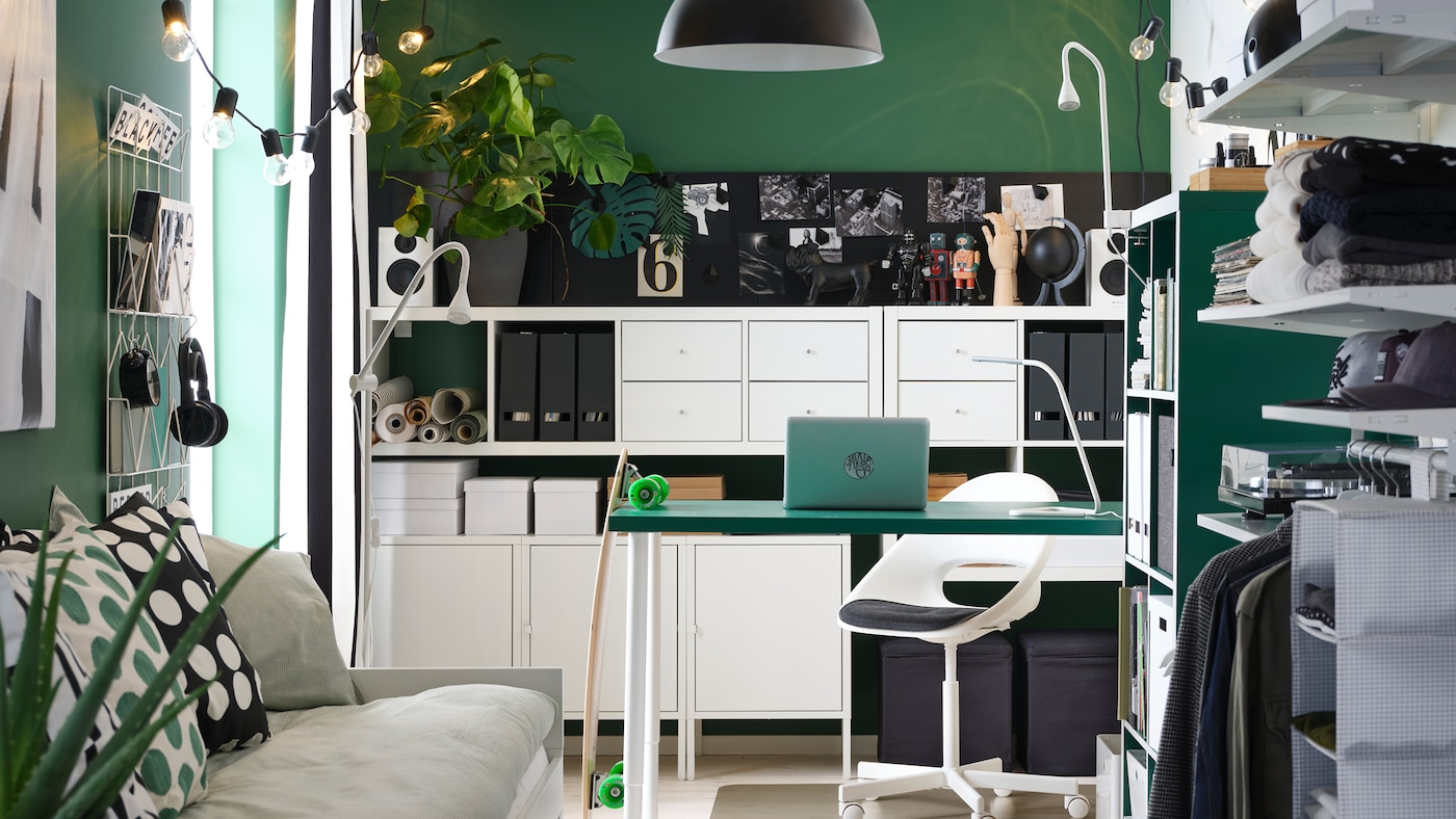A small room with a green table, white shelving units, a day-bed, an open wardrobe and a black pendant lamp.