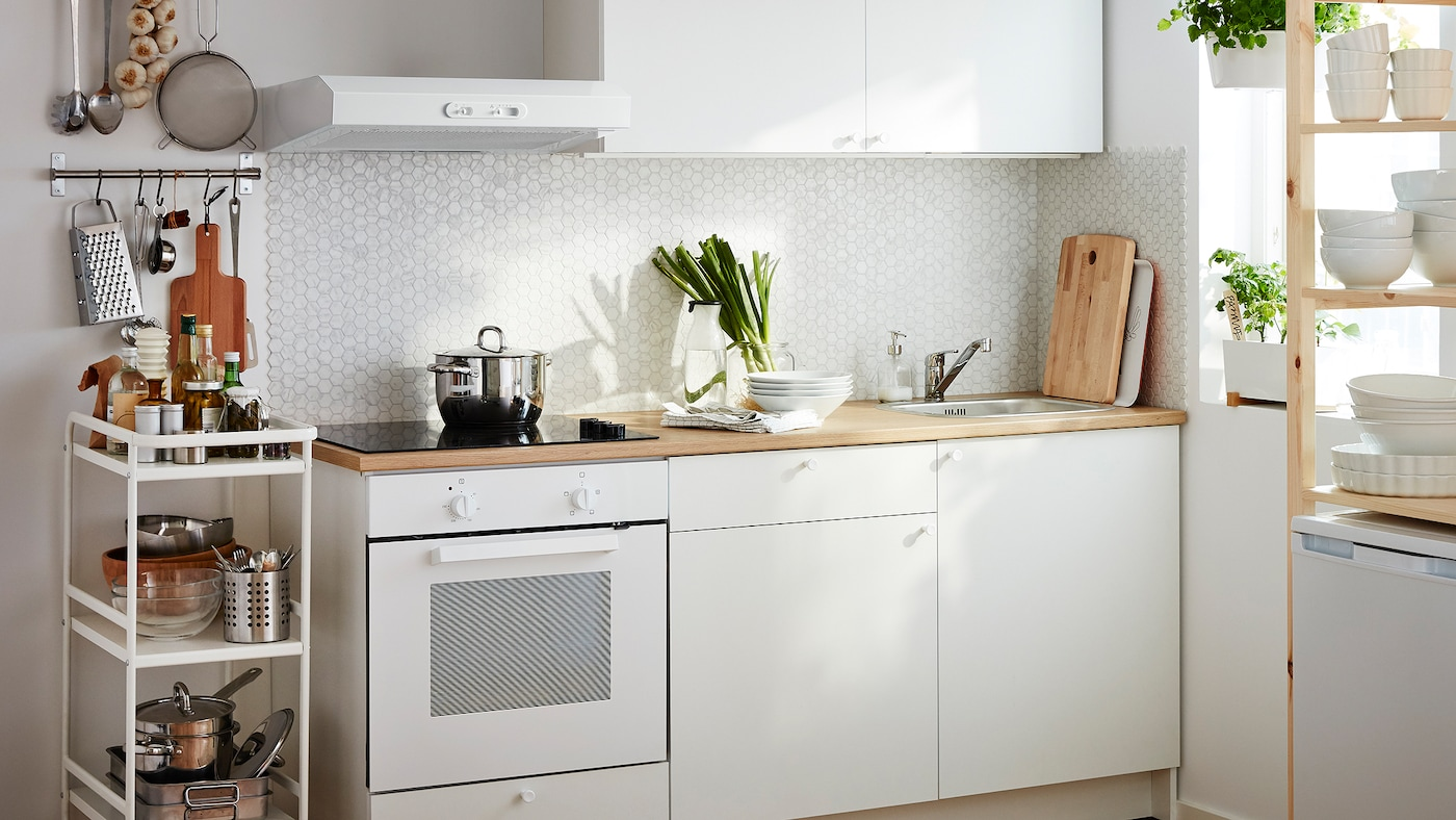 A small white kitchen consisting of a built-in oven and base cabinets, drawers, a worktop and a wall cabinet.