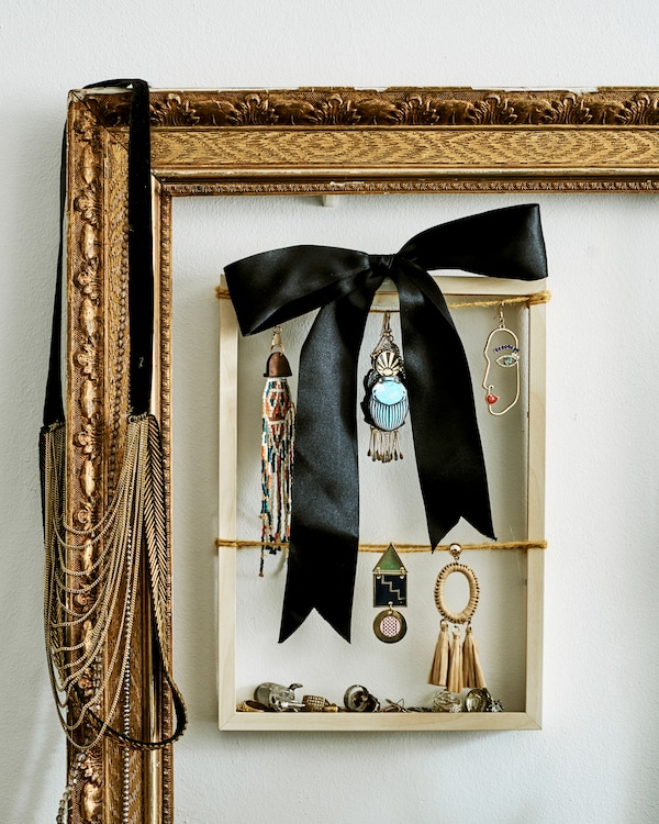 A small wood frame used to display dangly earrings and a black bow, hangs inside a large gilt frame.