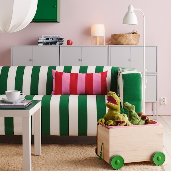 A sofa with green and white stripes, a red and pink striped cushion, a box of stuffed toys and some storage.