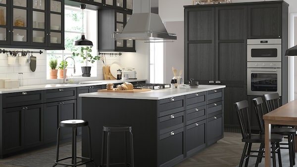 A spacious black and white kitchen in a classic style with stained black LERHYTTAN cabinet doors.