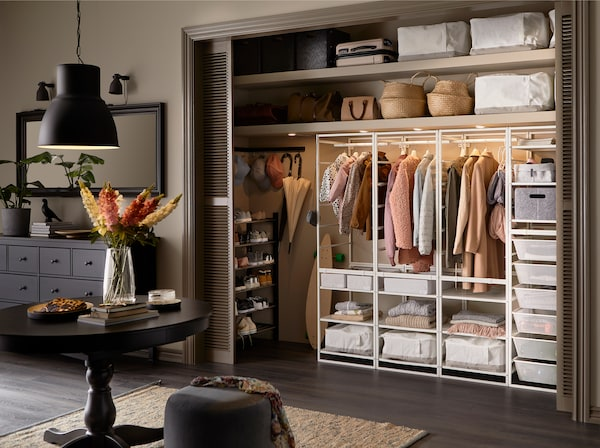 A spacious hallway with a built-in wardrobe with JONAXEL white storage system, white storage cases and lighting inside.