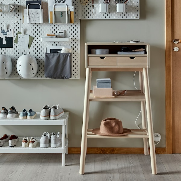 A standing desk in white birch, a white shoe shelf and white wall-mounted pegboards where helmets and more things are stored.