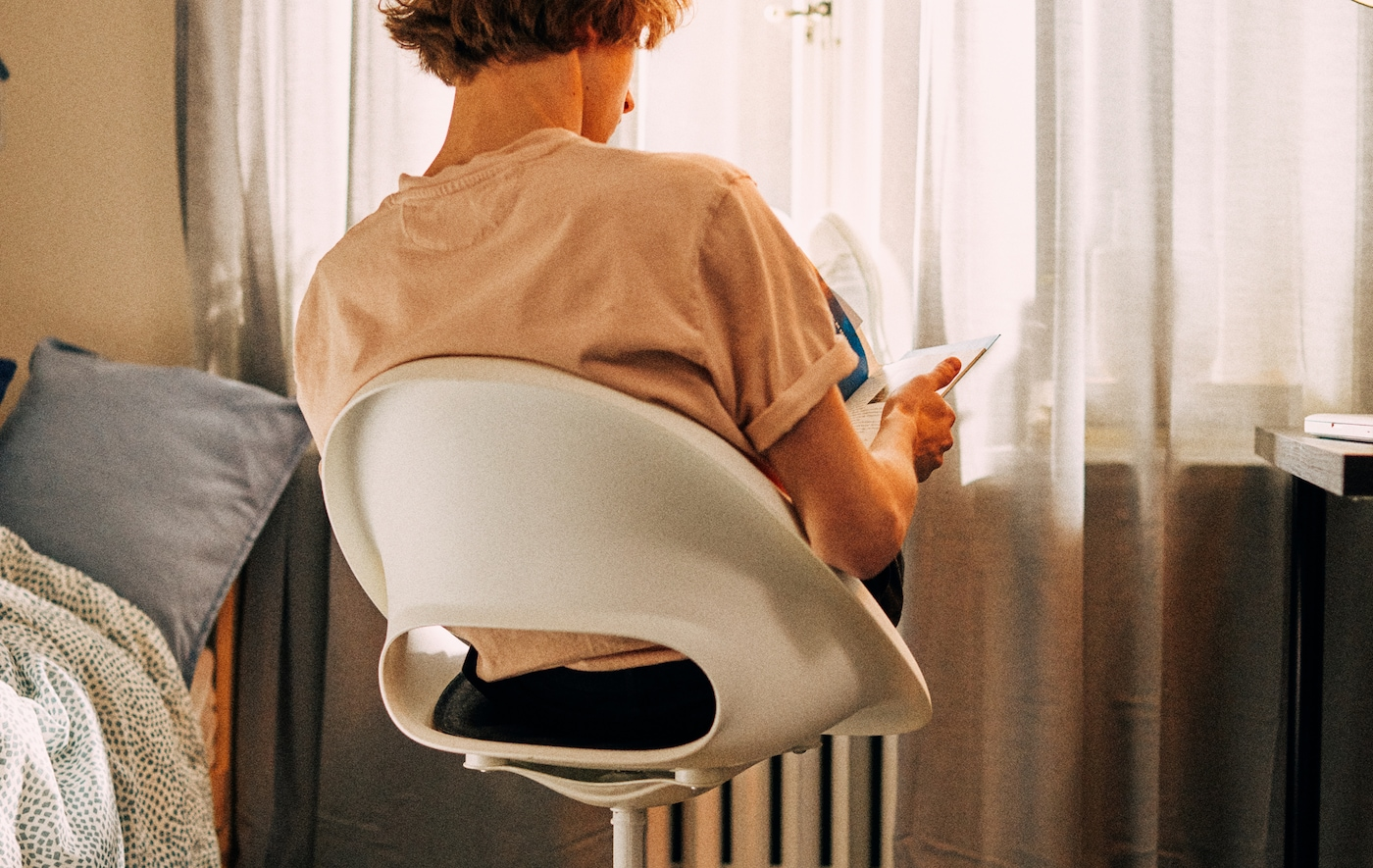A student sits in a swivel chair facing the window, his feet resting on the radiator in front of him as he studies.