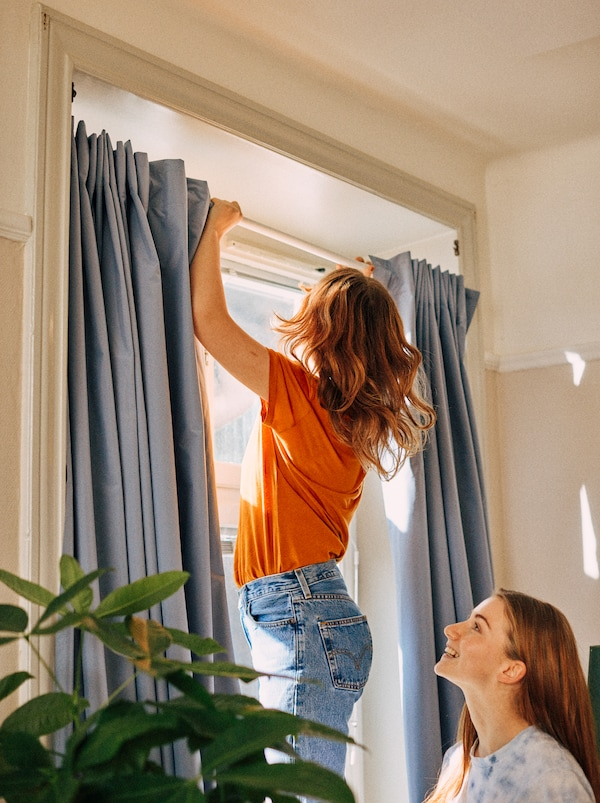 A student uses a shower curtain rod to install curtains in a window without drilling, while her friend looks on.