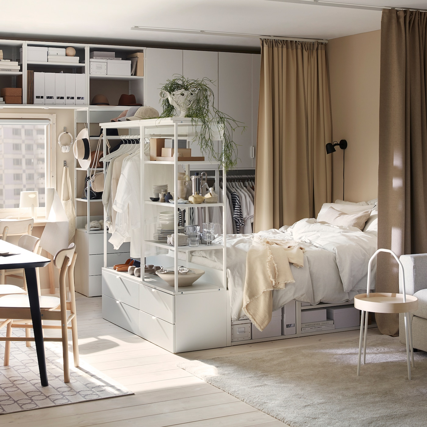 A studio flat with PLATSA storage combinations and bed frame in white, a black dining table and beige curtains.