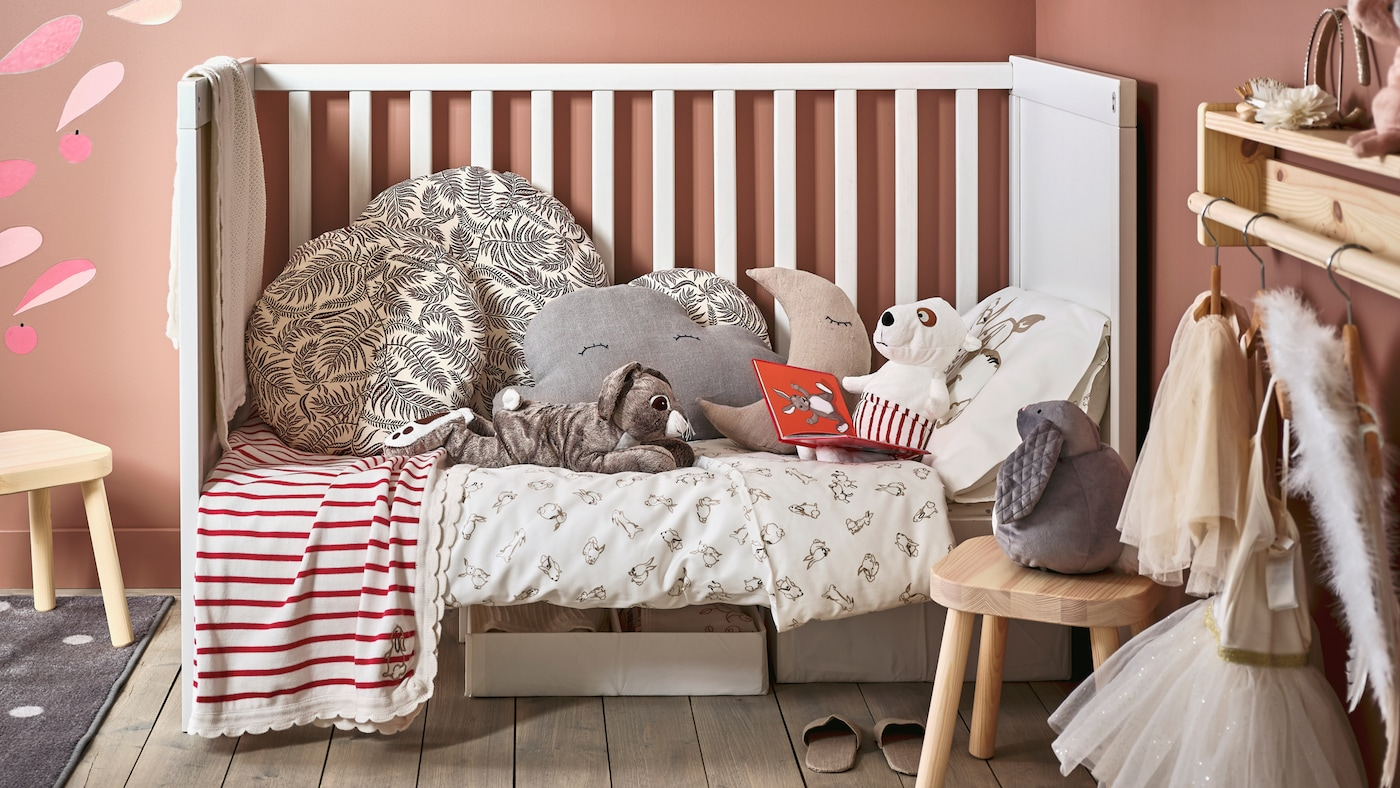 A SUNDVIK cot with RÖDHAKE bed linen, cosy cushions and soft toys sits in the corner of a child's bedroom.