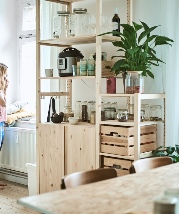 A tall wooden storage unit in a kitchen/diner with glass jars, wood crates and kitchen gadgets on the shelves.