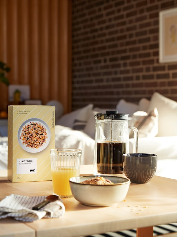 A tasty breakfast arranged on a living-room table, including a glass of juice, a carafe of coffee and HJÄLTEROLL muesli.