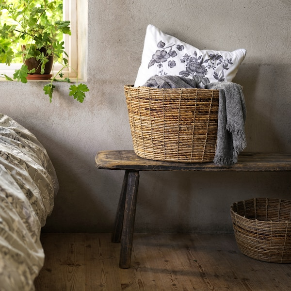 A TJILLEVIPS basket made from banana fibre is filled with blankets and a white floral cushion and placed on a bench.