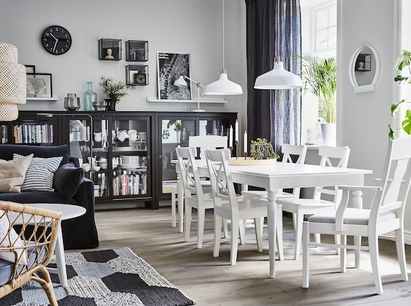 A traditional style, dining area beside the sitting room with extendable white INGATORP dining table and INGATORP chairs with soft padded seats. The HEMNES glass door cabinet in black provides space to store dinnerware.
