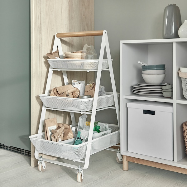 A trolley on castors with three steel mesh baskets where snacks, dry goods and bowls are stored. It stands next to a cabinet.