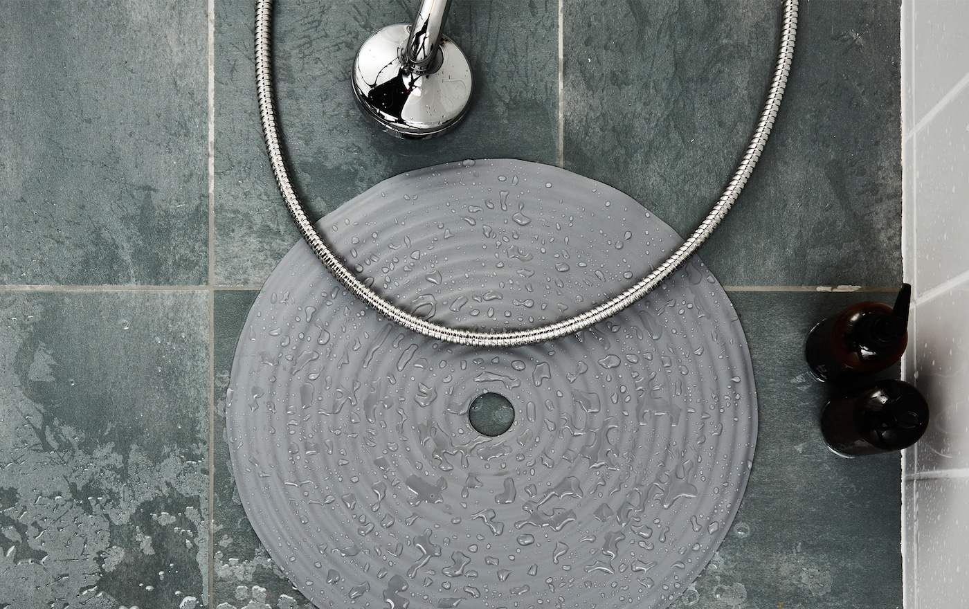 A tub mat sits on the floor of a wet shower.
