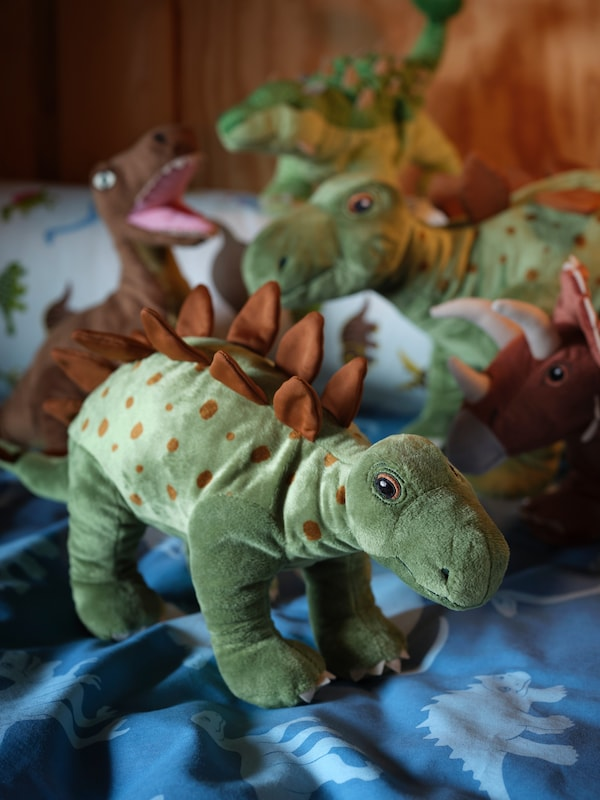 A variety of different dinosaurs from the JÄTTELIK range of soft toys are gathered on a dinosaur quilt.