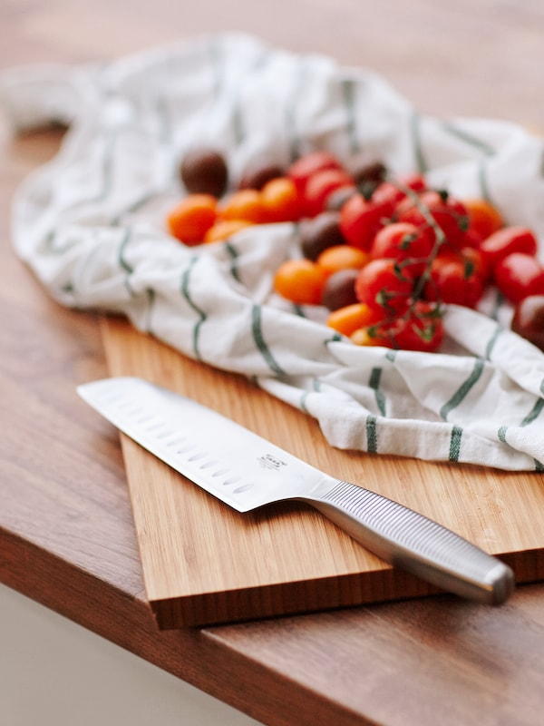 A vegetable knife in stainless steel on a wooden chopping board next to tomatoes on top of a tea towel.