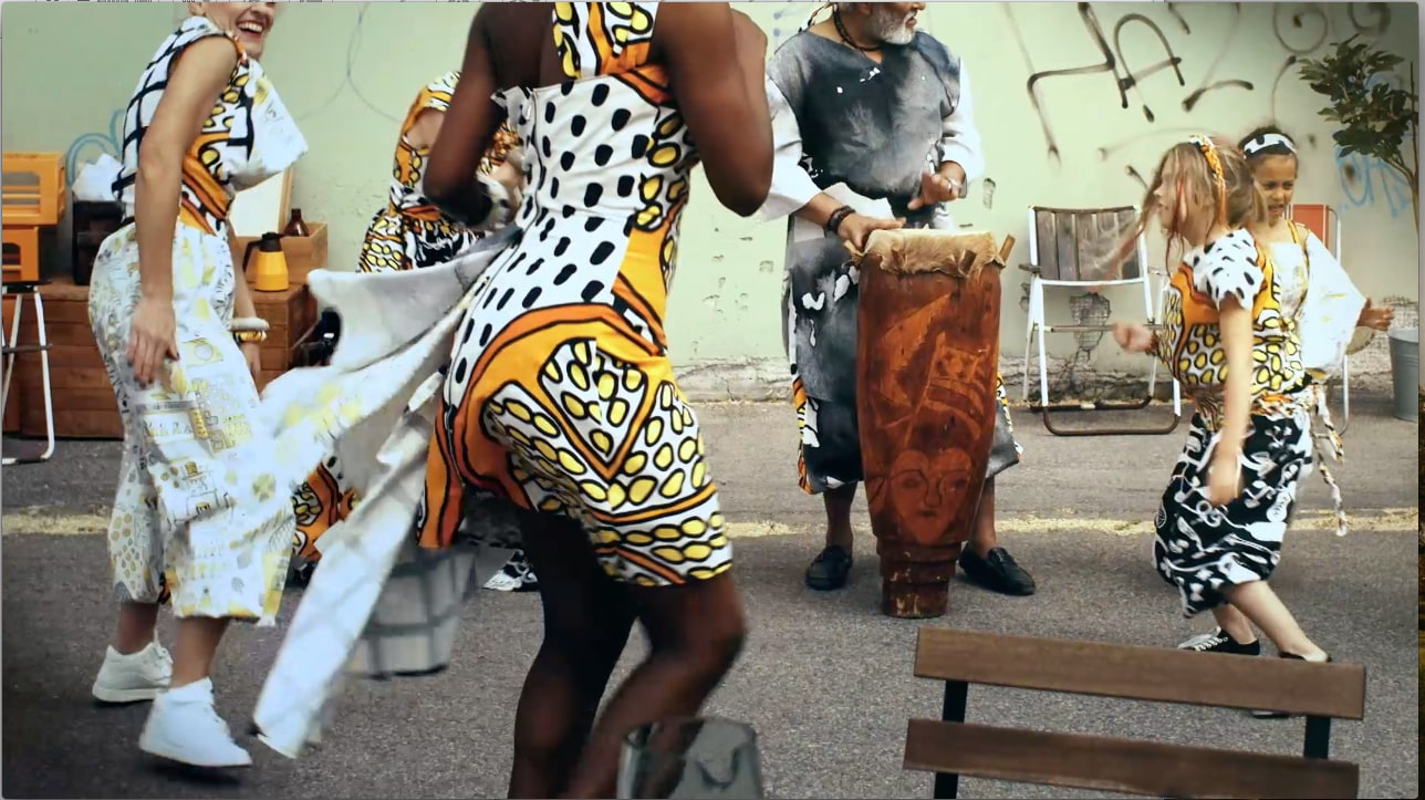 A video showing dancing people dressed in clothes made of fabrics with patterns of plants, kitchen utensils and food.