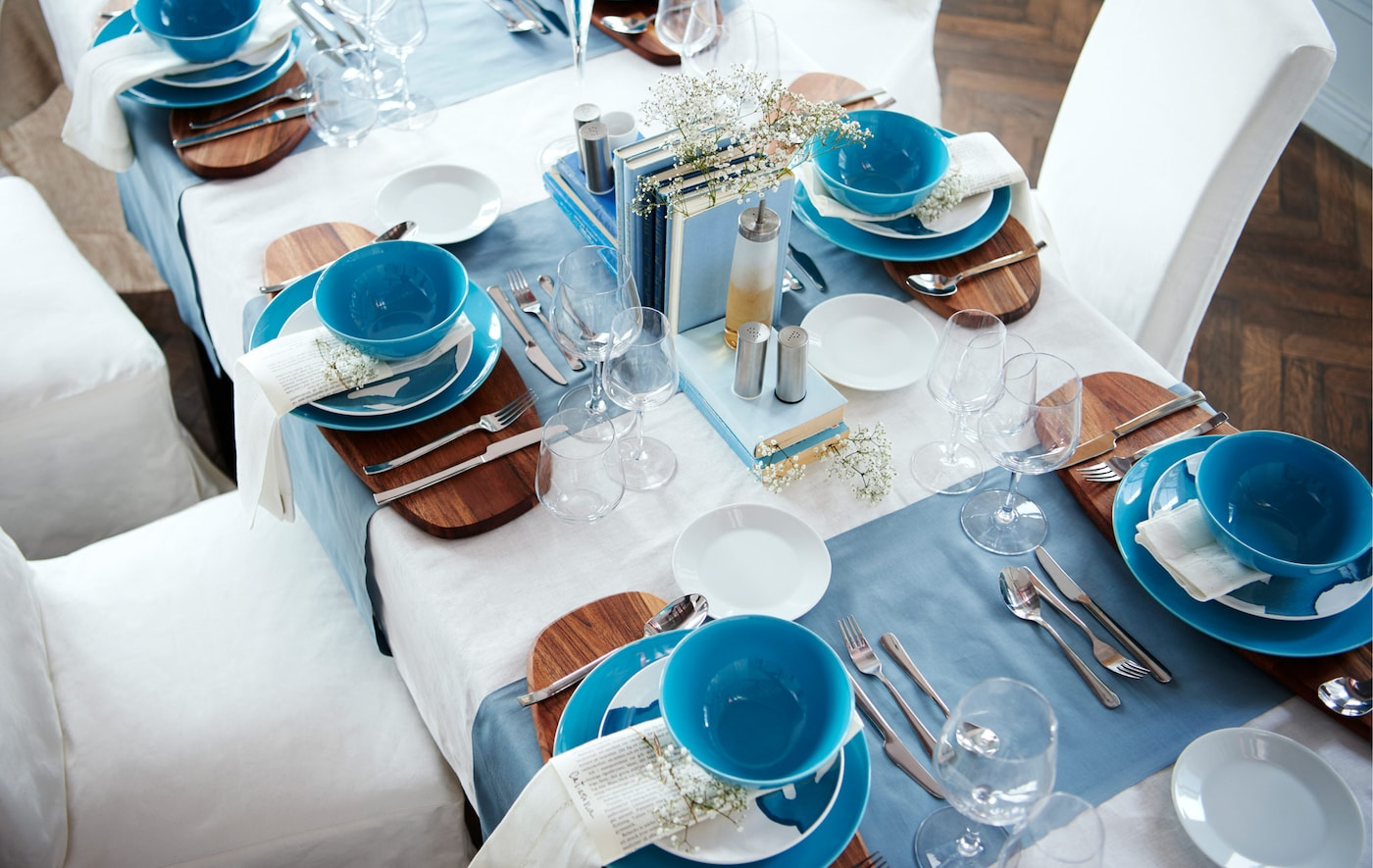 A view from above of a dining table set formally with a white and blue colour scheme.