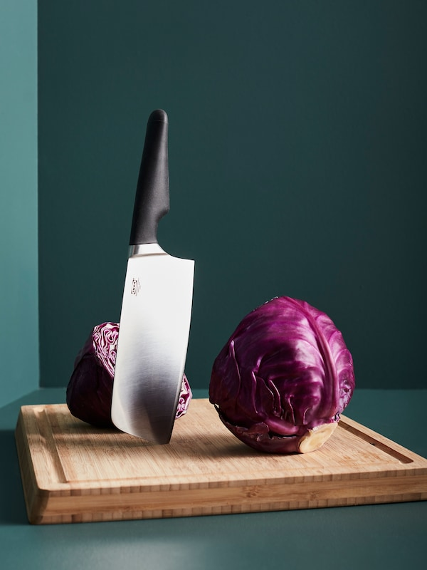 A VÖRDA Chinese chopper with a black handle stands vertically on an APTITLIG butchers block in bamboo next to red cabbage.