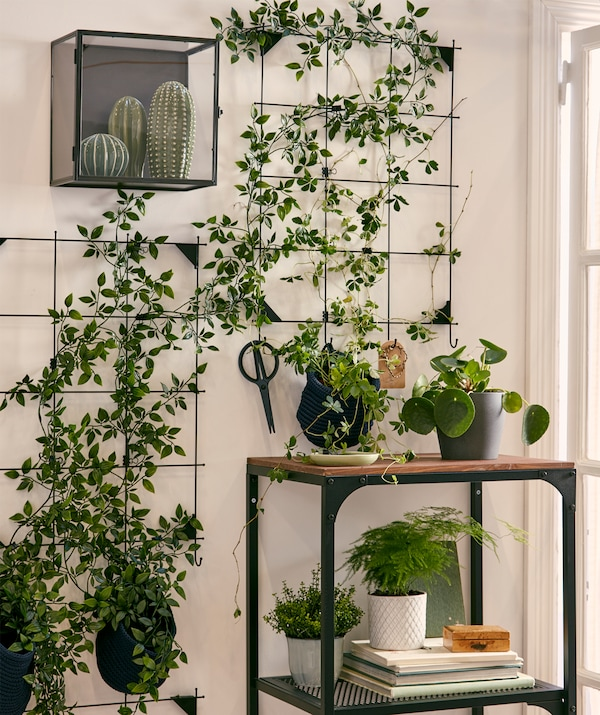 A wall garden formed using artificial plants attached to sections of wire memo board, framed by other real and fake plants.