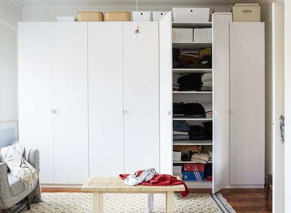 A wall of white wardrobes with storage boxes on top and a rattan coffee table in front.