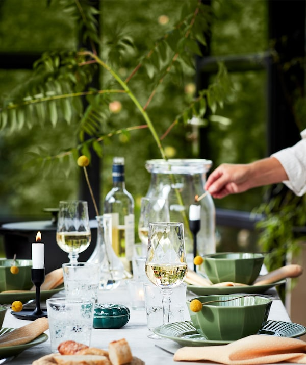 A well-laid table set for a dinner outdoors with green plates, wine glasses, candles and lots more. Shown with nature.