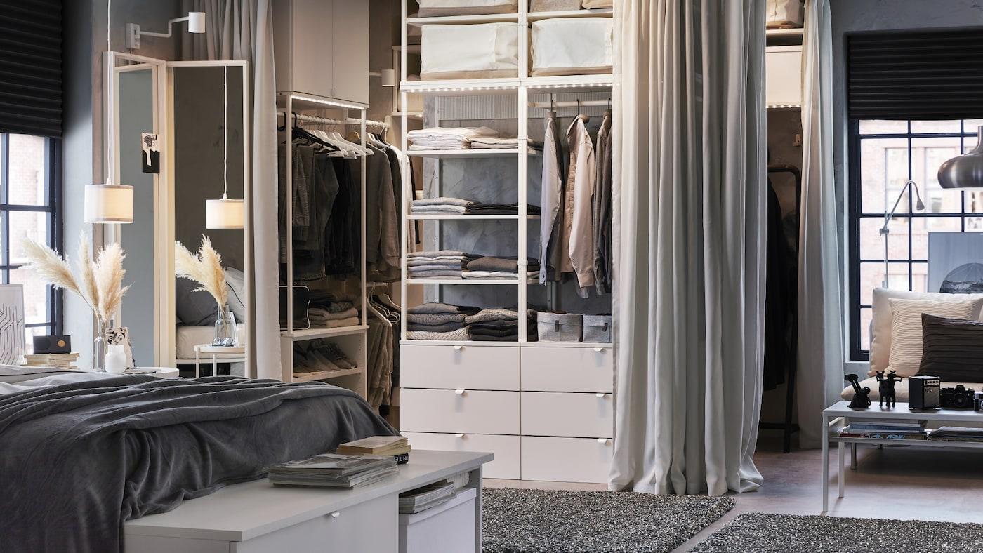 A white and grey bedroom with an open wardrobe, light grey curtains and dark grey rugs.