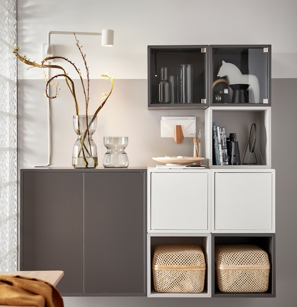 A white and grey EKET storage unit combination with two SMARRA storage boxes, two glass vases and personal items on display.
