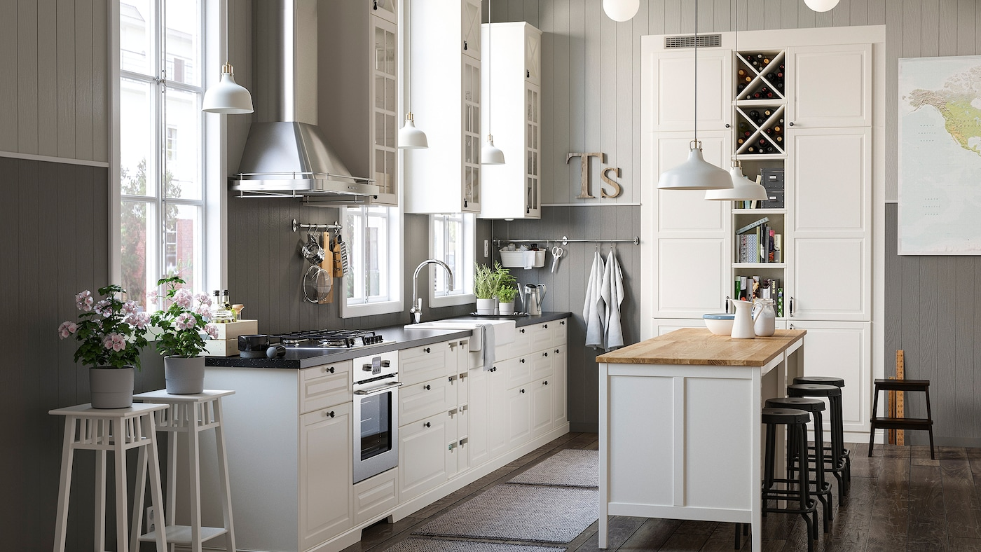 A white and grey rustic kitchen with a mix of closed and open white kitchen storage shelves and cabinets and an island.