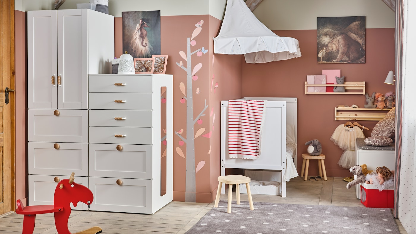 A white and pink traditional children's room with SMÅSTAD storage, a SUNDVIK cot, and FLISAT children's stools.
