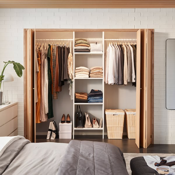 A white AURDAL wardrobe combination with shelves and rails is mounted in a space behind foldable wooden doors.