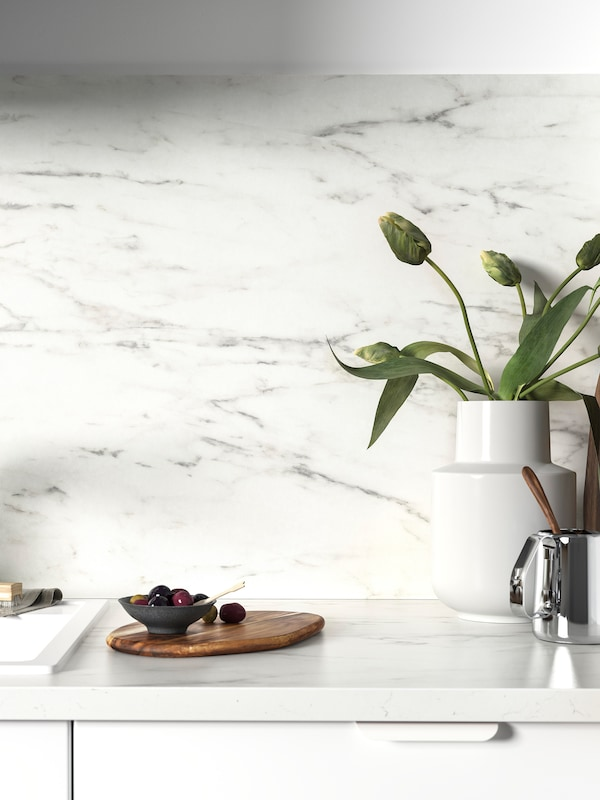 A white backsplash and white marble effect kitchen worktop blend together. A white vase with flowers stands on top.