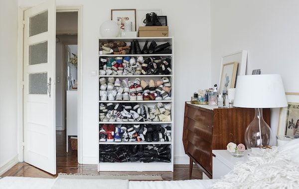 A white bedroom with wooden floors and shoes stacked in a bookcase.