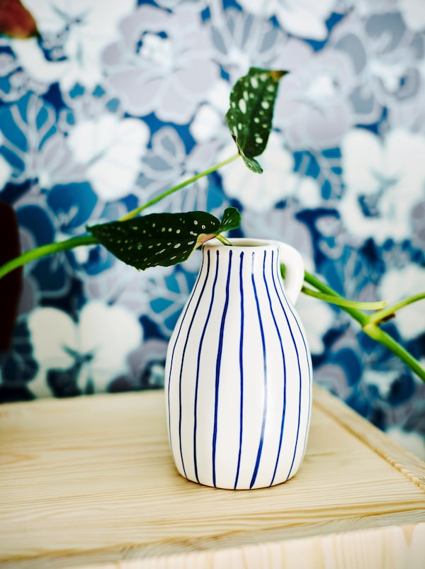 A white ceramic vase with irregular blue stripes holding a plant in front of a blue and white floral wallpaper print.