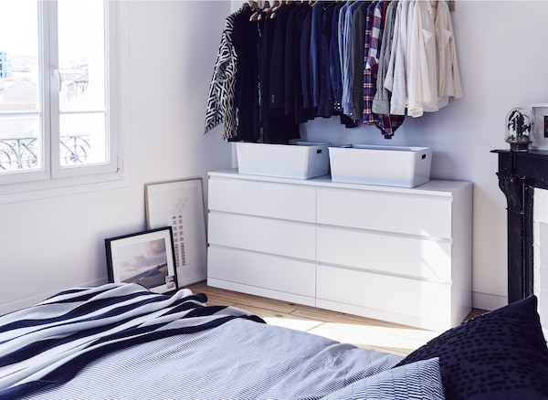 A white chest of drawers and clothes hanging in a bedroom.